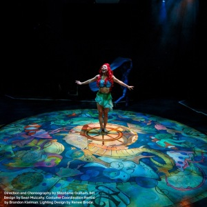 Ariel, the mermaid, dancing on the stage. The lights make it look like she is underwater and giant pieces of seaweed hang from the ceiling around her furthering the illusion.