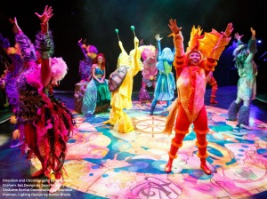 Cast members in a variety of brightly coloured costumes depicting sea creatures dancing around Ariel, the mermaid.